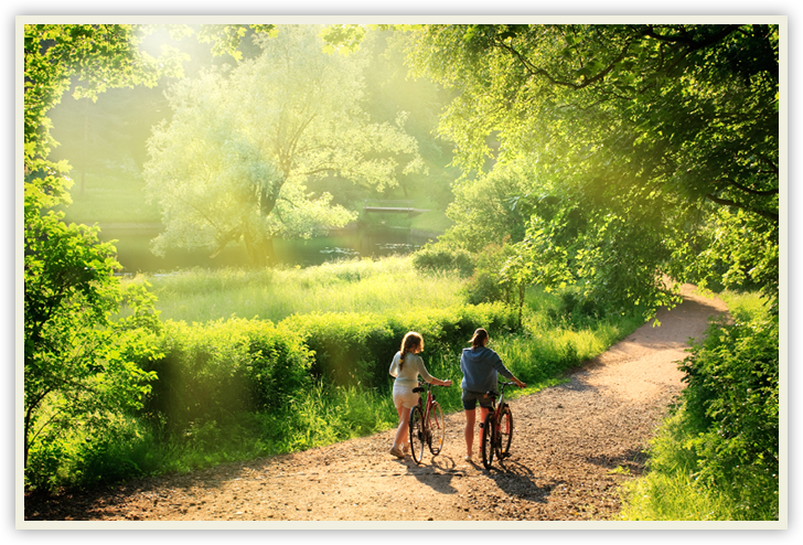 couple walking bikes down path